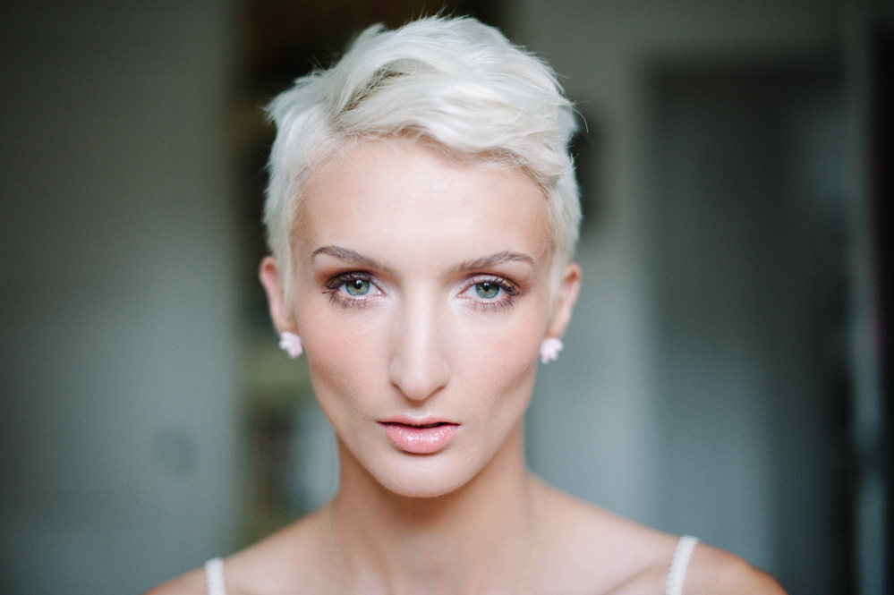 Portrait of a young woman with short white hair by Briana Morrison