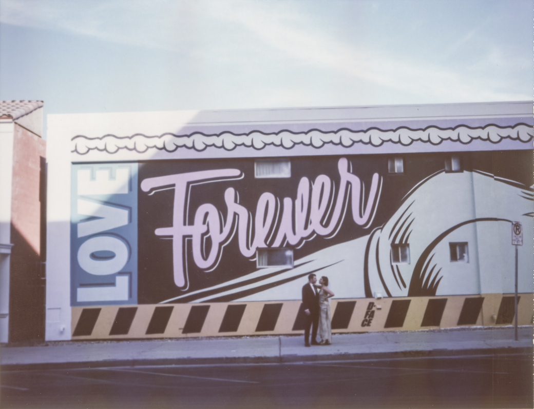 "Polaroid of newlyweds in front of a ""Love Forever"" mural in Las Vegas, Nevada. Captured by Las Vegas Elopement Photographer Briana Morrison"