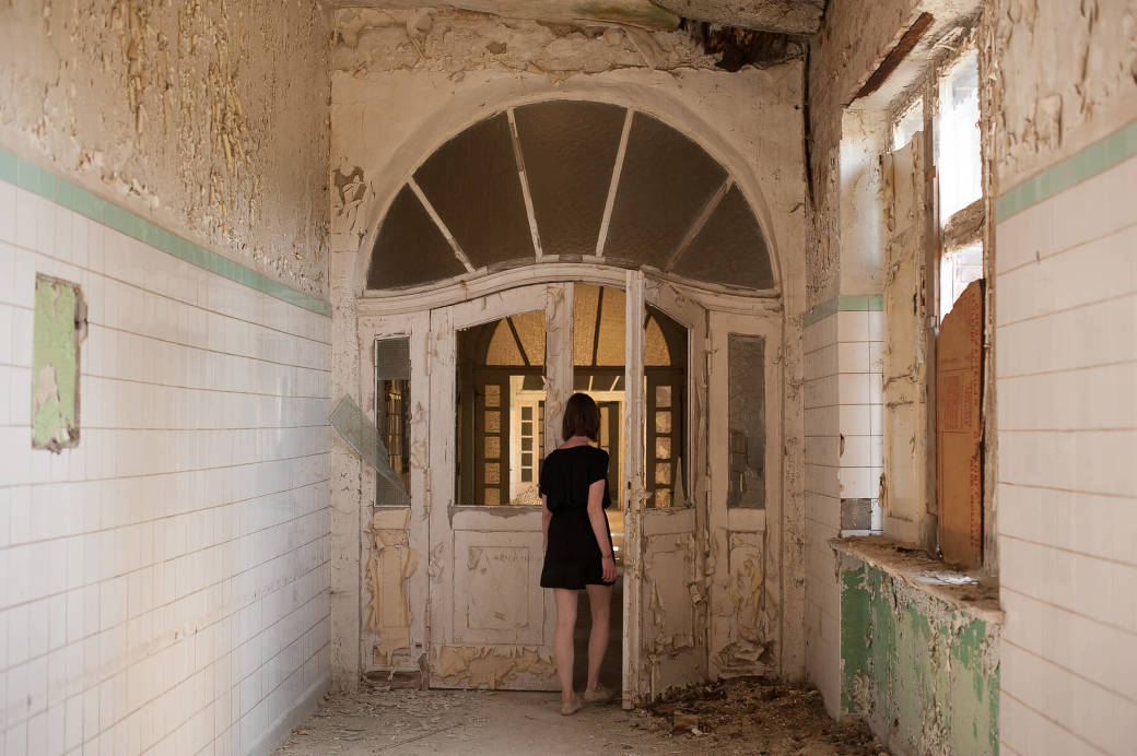Yvonne walking through a doorway at the Heilstätten Hohenlychen Sanitorium in Germany. Photography by Briana Morrison