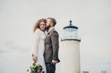 A bride and groom in front of the Cape Disappointment Lighthouse in Washington. Pacific Northwest Wedding Photographer