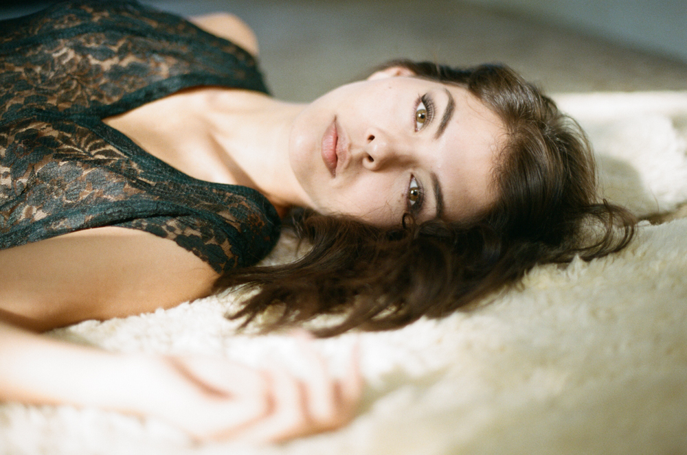 Leah Morris posing on a sheepskin rug for a film bohemian boudoir session with Briana Morrison