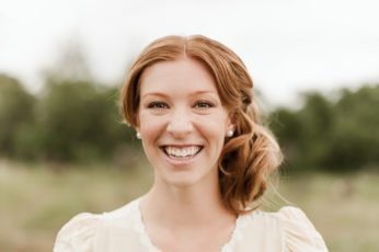 A portrait of a smiling redheaded woman in a field. By Chico portrait photographer Briana Morrison