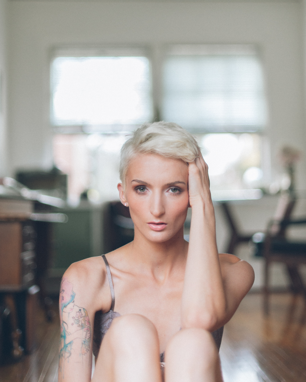 Boudoir portrait of a young woman in front of a window with her hand in her short blond hair.  Photograph by Briana Morrison
