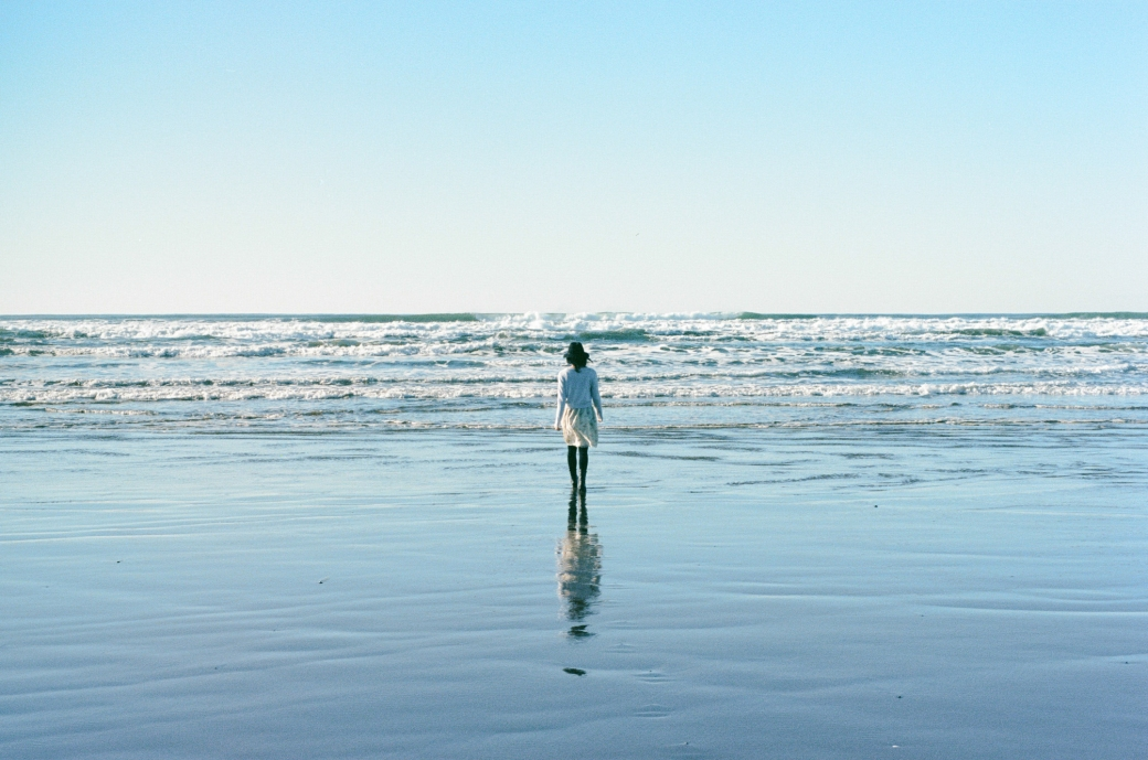 Portrait of a young woman walking into the blue ocean by Briana Morrison