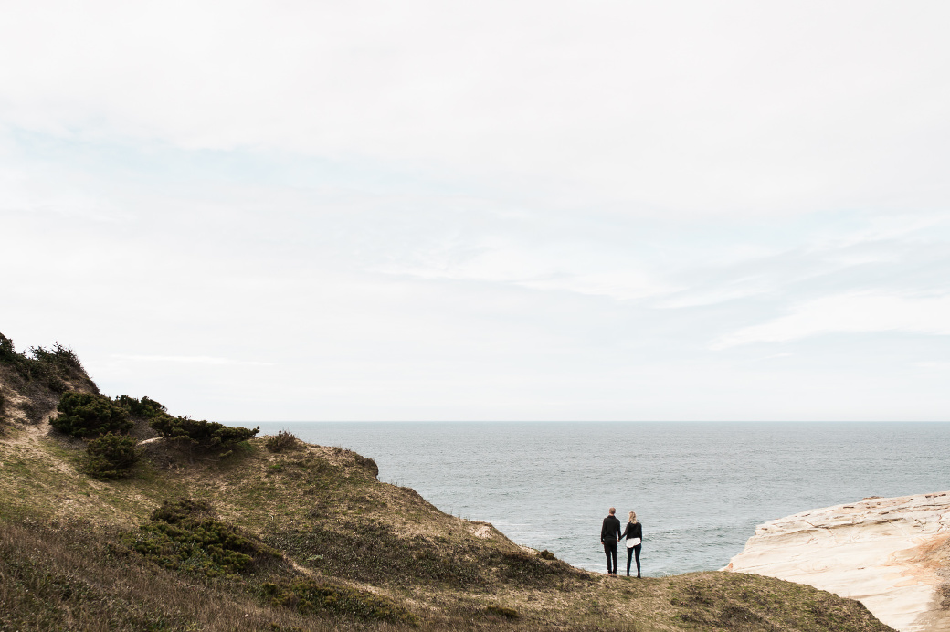 A young couple soak in the view at Cape Kiwanda in Oregon. Cape Kiwanda Engagement Photographer Briana Morrison