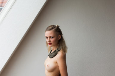 Beautiful portrait of a blonde woman in a black spiked collar by Berlin boudoir photographer Briana Morrison