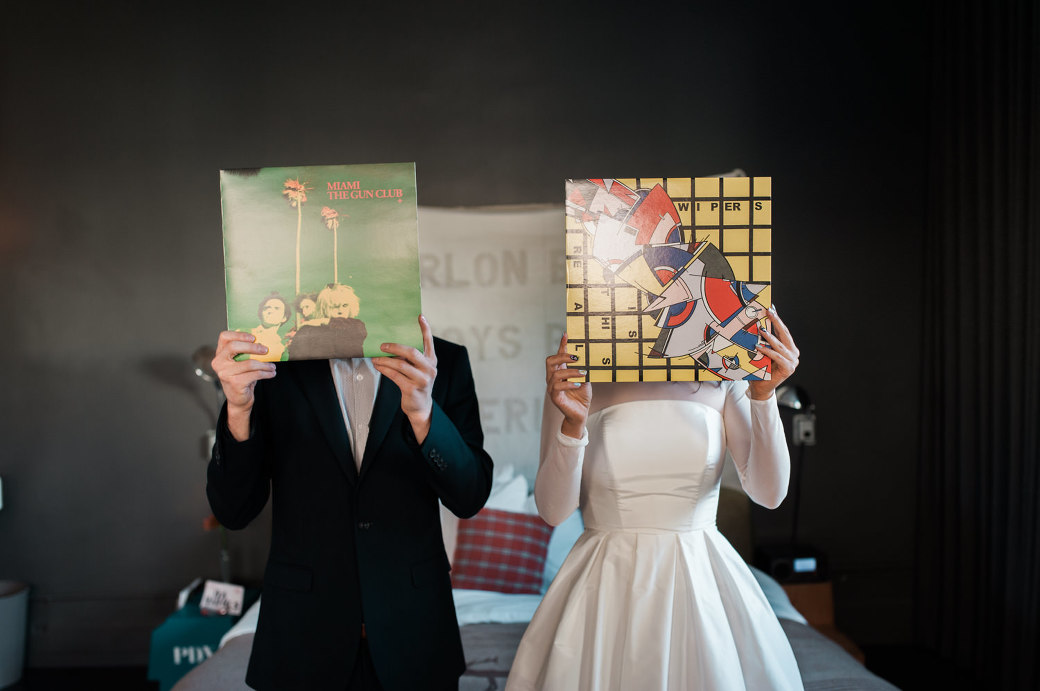 A bride and groom holding records over their faces. By Ace Hotel wedding photographer Briana Morrison