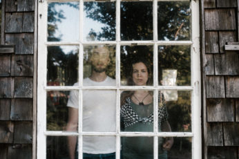 Portrait of a young couple standing behind a window. By Portland Maternity Photographer Briana Morrison