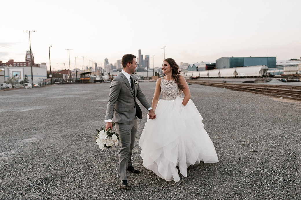 A bride and groom in front of the Seattle skyline. By Sodo Park wedding photographer Briana Morrison