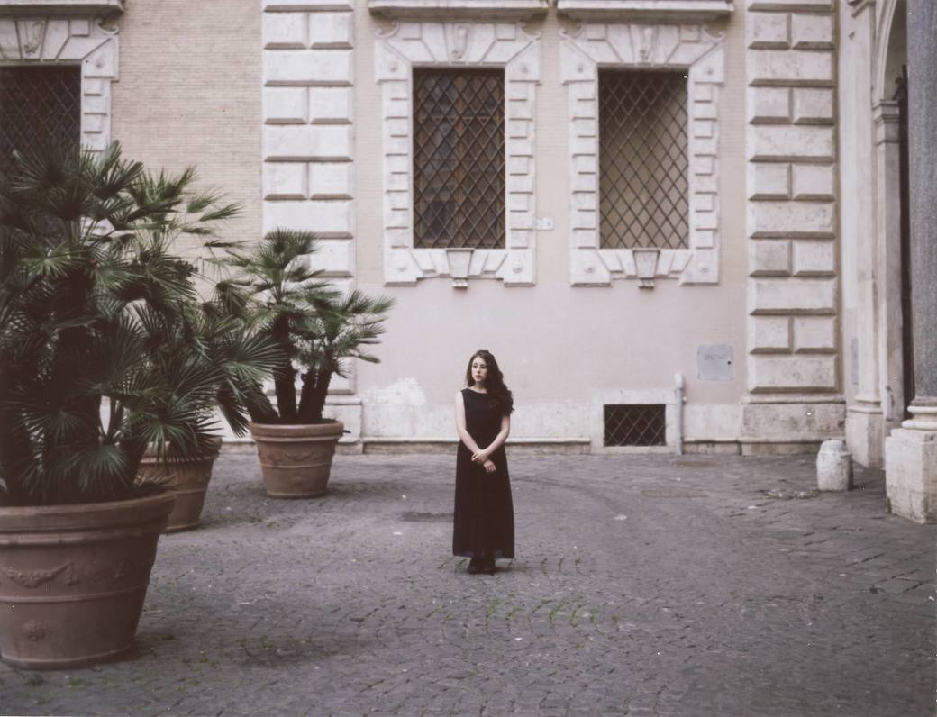A young woman stands in the courtyard of an old cathedral in Rome, Italy. By Rome portrait photographer Briana Morrison